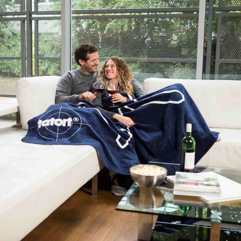 Ein Paar mit der Kuscheldecke Tatort-Kolter auf der Couch