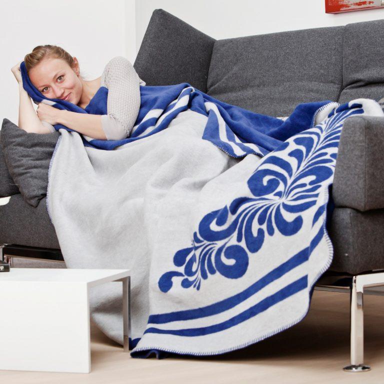 Frau mit der Kuscheldecke Bembel-Kolter auf der Couch
