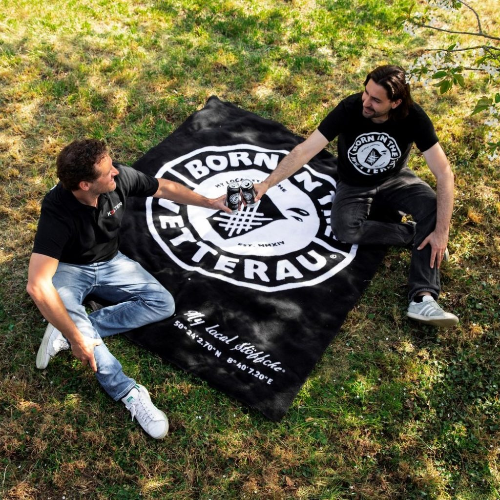 Zwei Männer mit der Decke Born in the Wetterau Kolter auf einer Wiese