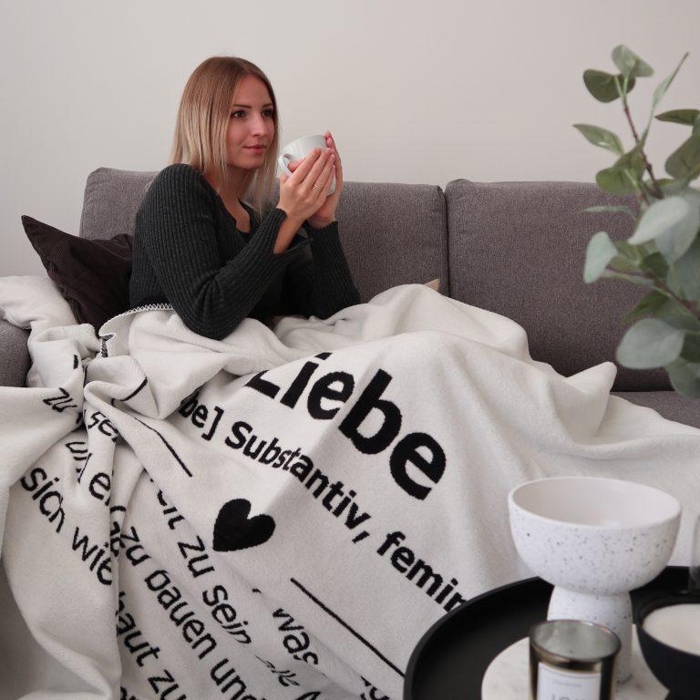 Frau mit der Kuscheldecke Liebe-Kolter auf der Couch