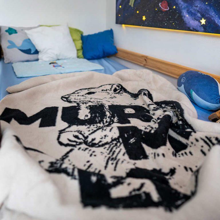 Kuscheldecke Murmeli-Kolter auf dem Bett