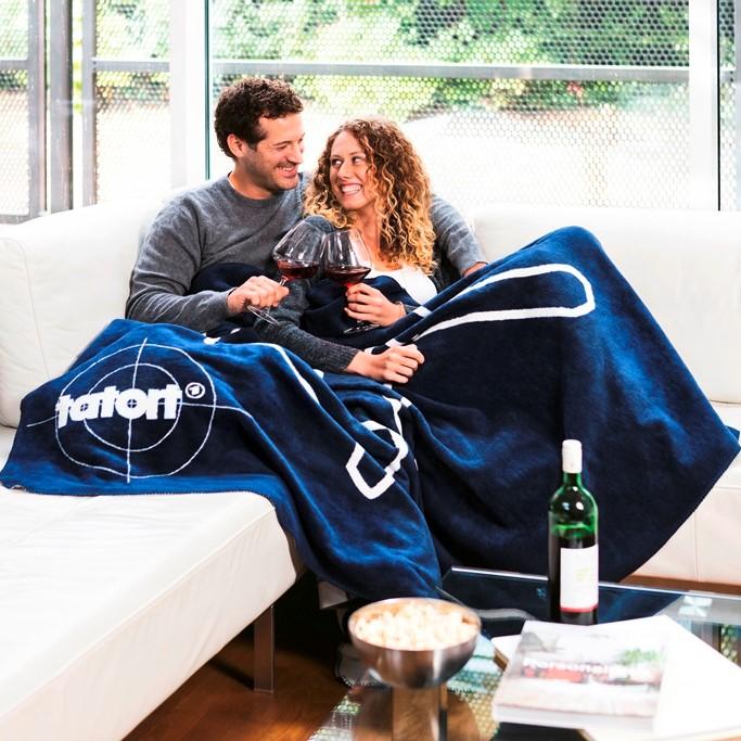 Paar mit der Kuscheldecke tatort-Kolter-Decke auf der Couch