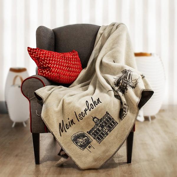 Kuscheldecke Iserlohn-Kolter drapiert auf einem Sessel